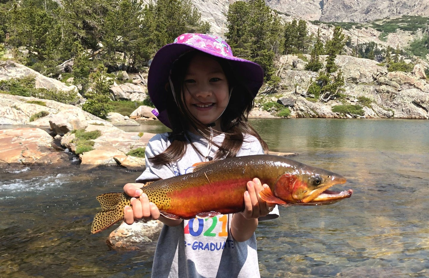 Girl holding record golden trout next to a lake.