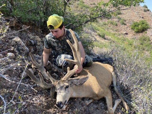A young hunter admires the rack of a big mule deer.