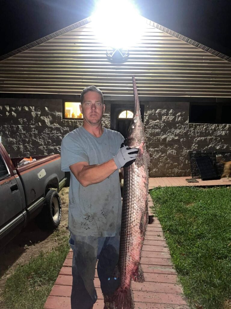 man holds gar vertically at night in front of a building