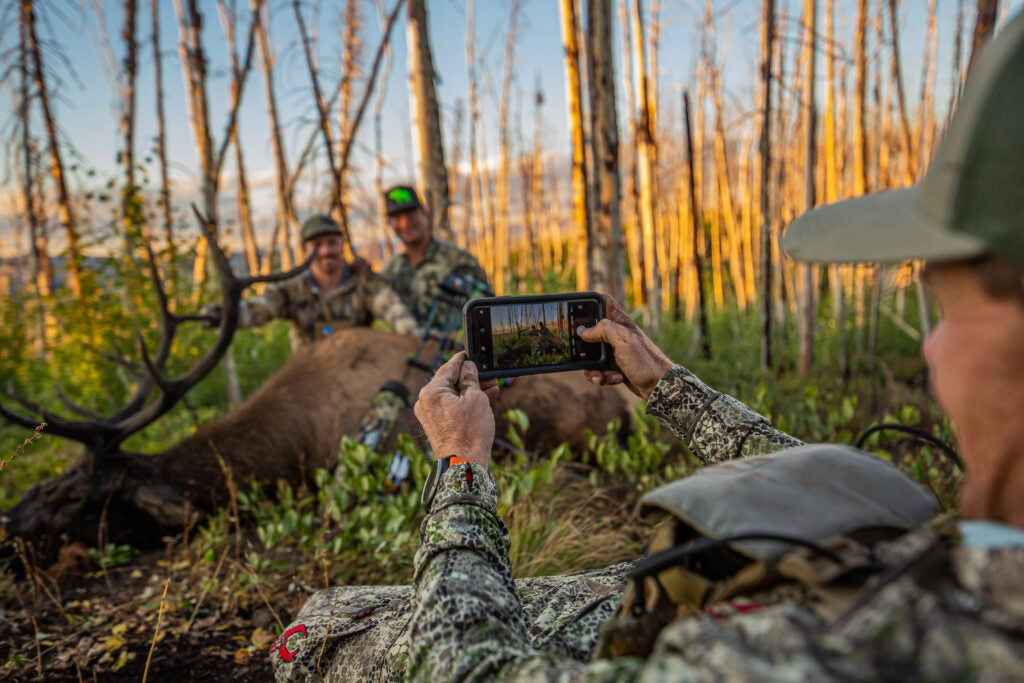 Jace Bauserman takes picture of bull elk.