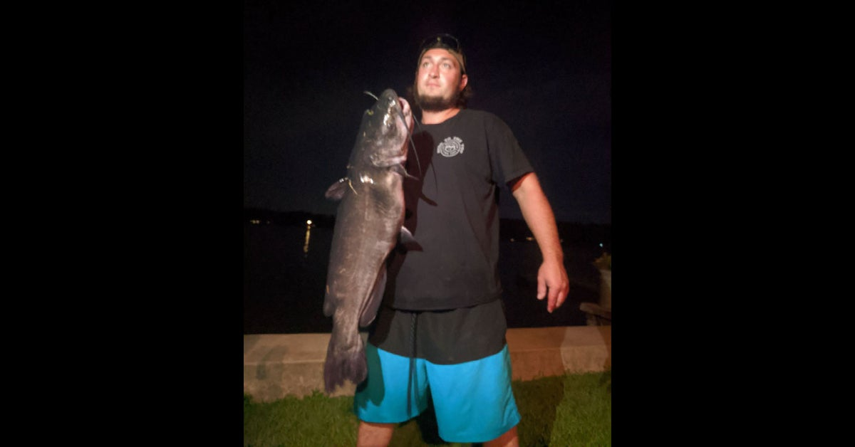 man in black shirt and blue shorts holds large catfish vertically