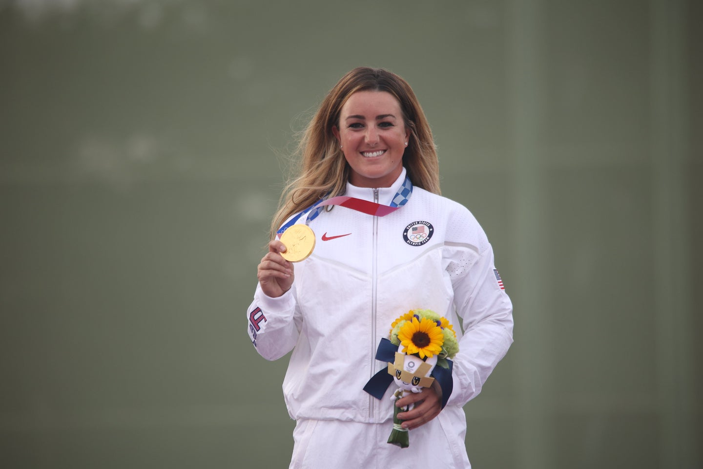 Lt. Amber English standing with an olympic gold medal for skeet shooting.