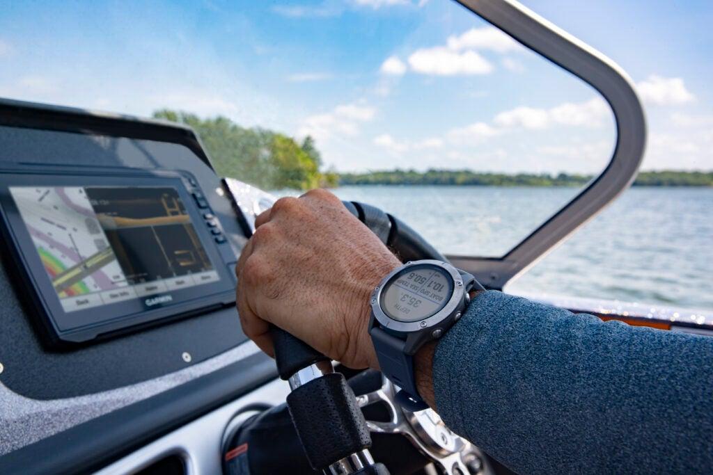 Fisherman driving boat and looking at fish finder