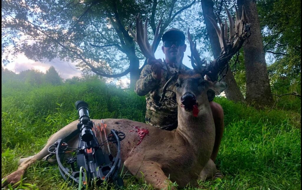 a hilt and a smile with a huge white-tailed buck with a crossbow leaning against his hindquarters