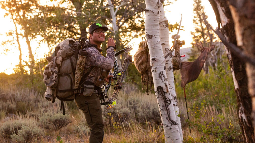 A hunter in the woods making an elk call.