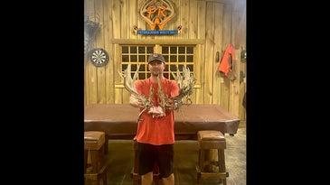 man in orange shirt holding deer antlers