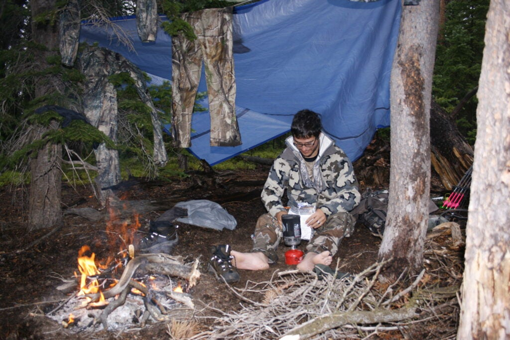Hunter sitting under a tarp with a fire.