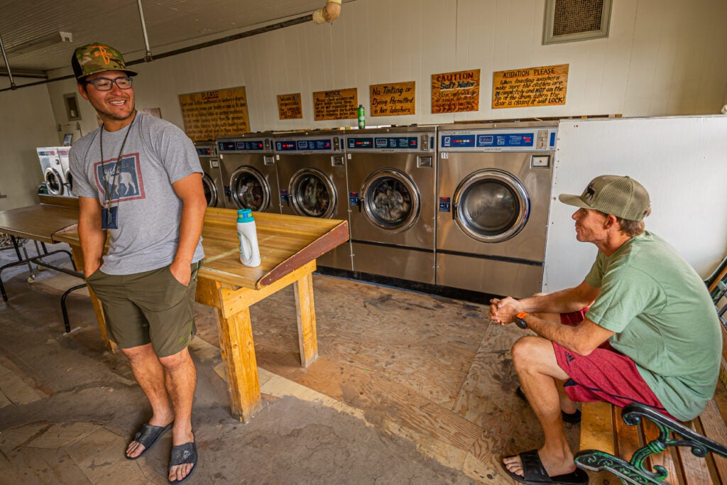 Two men sitting at the laundromat.