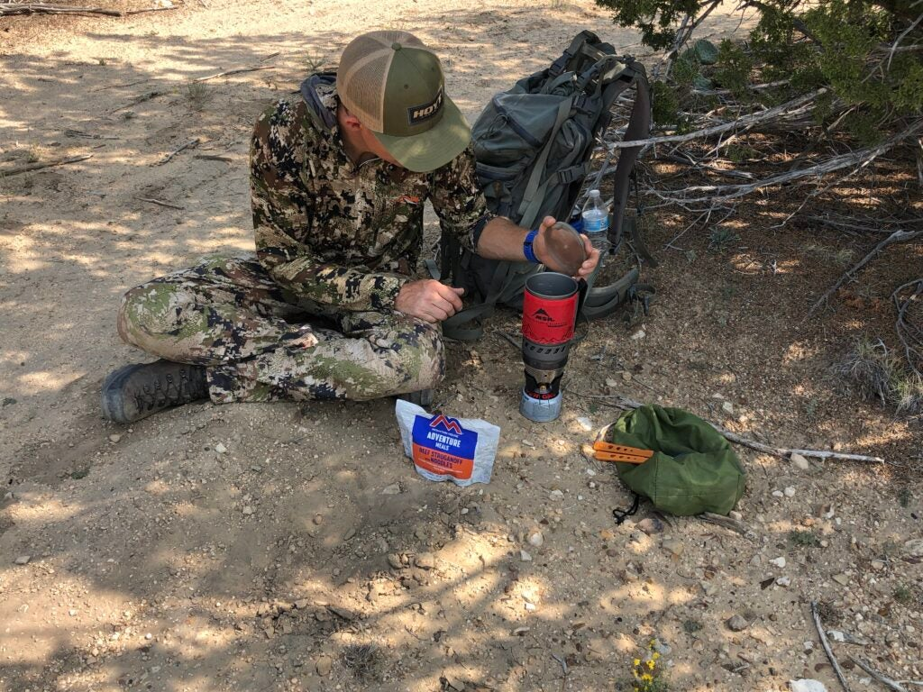 Hunter cooking on the ground with a portable stove.