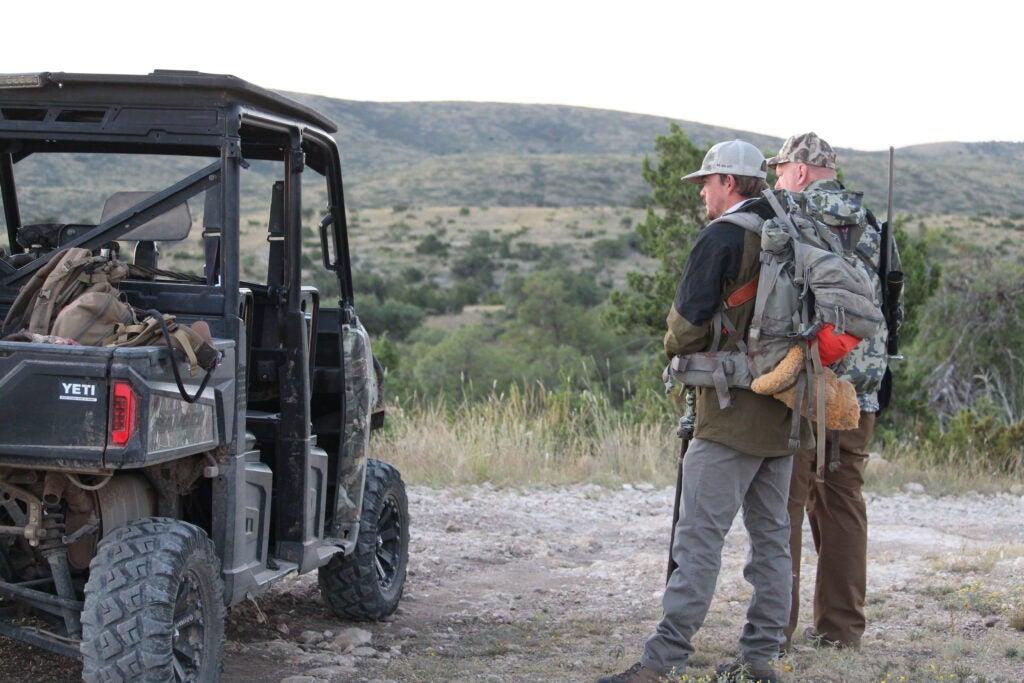 Hunters standing near a UTV.