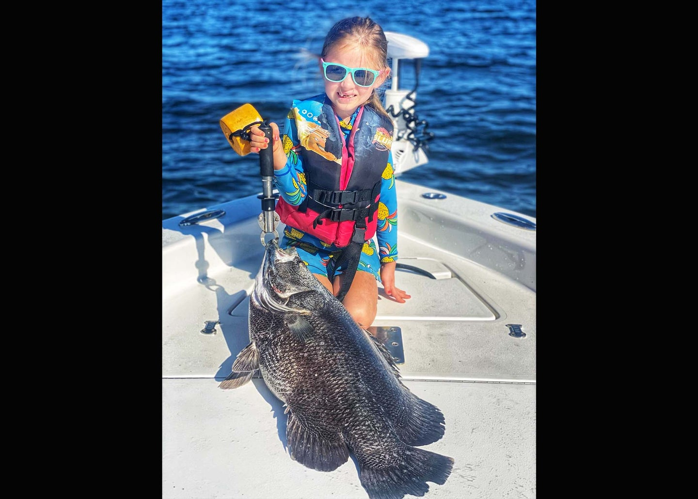 A small girl in life vests on boat with big black fish