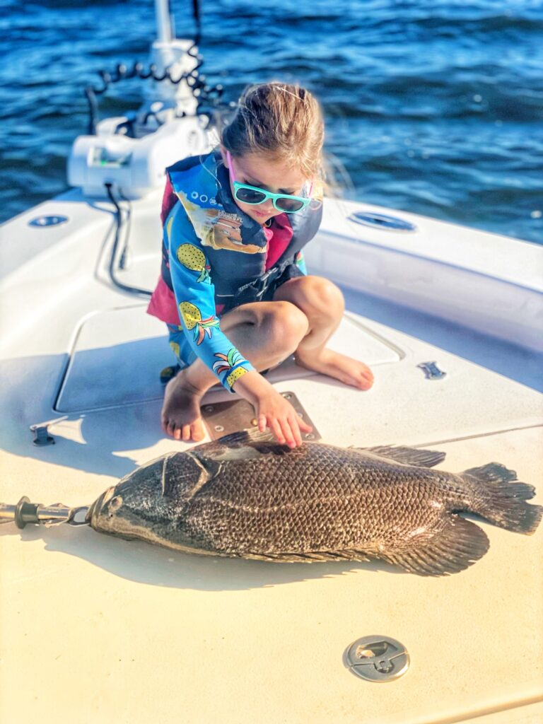 young angler strokes fish on boat