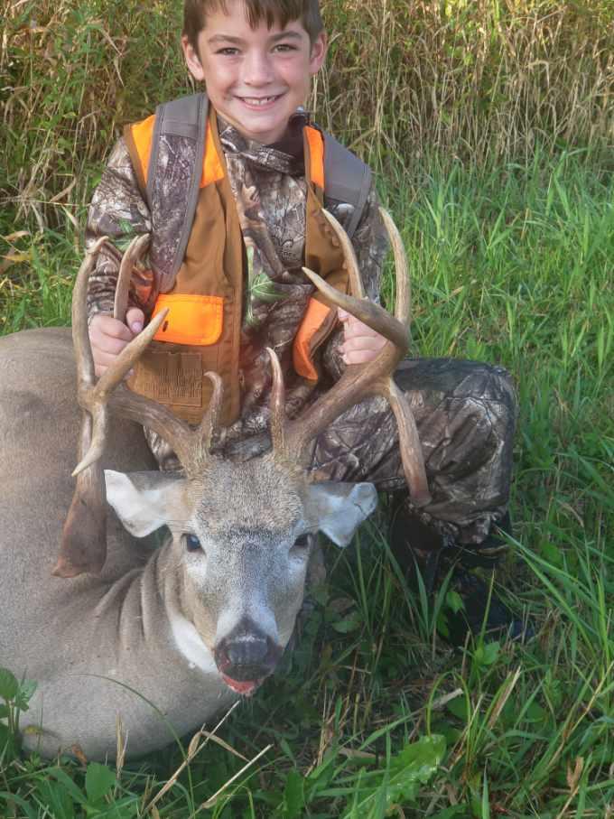 Boy wearing fluorescent orange vest poses with dead triple drop tine deer