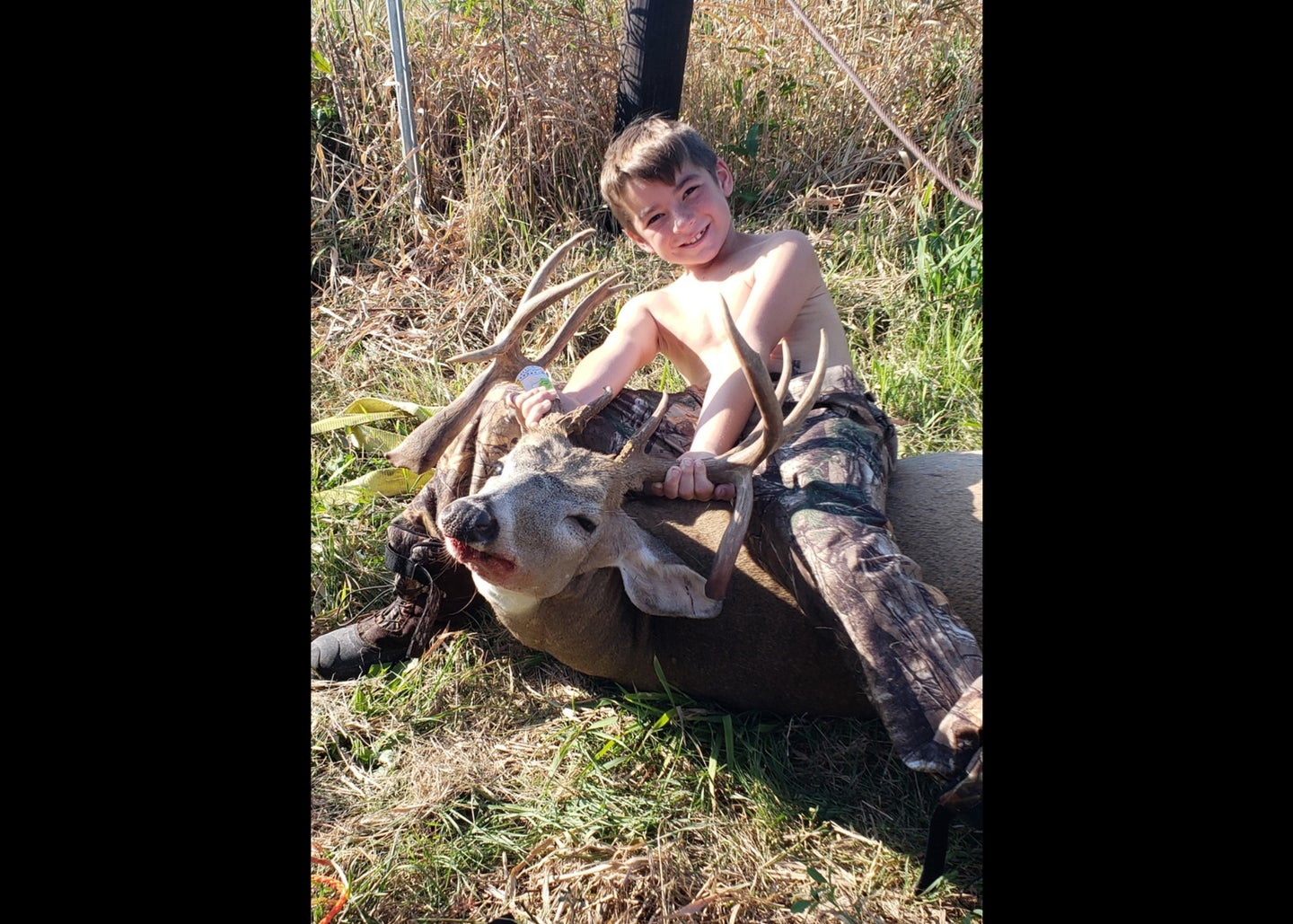 shirtless boy poses with deer with wild rack with three horns that jut down