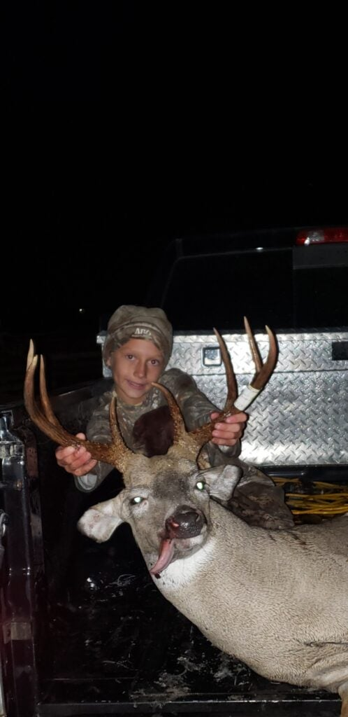 Young boy poses with dead deer with sizeable rack