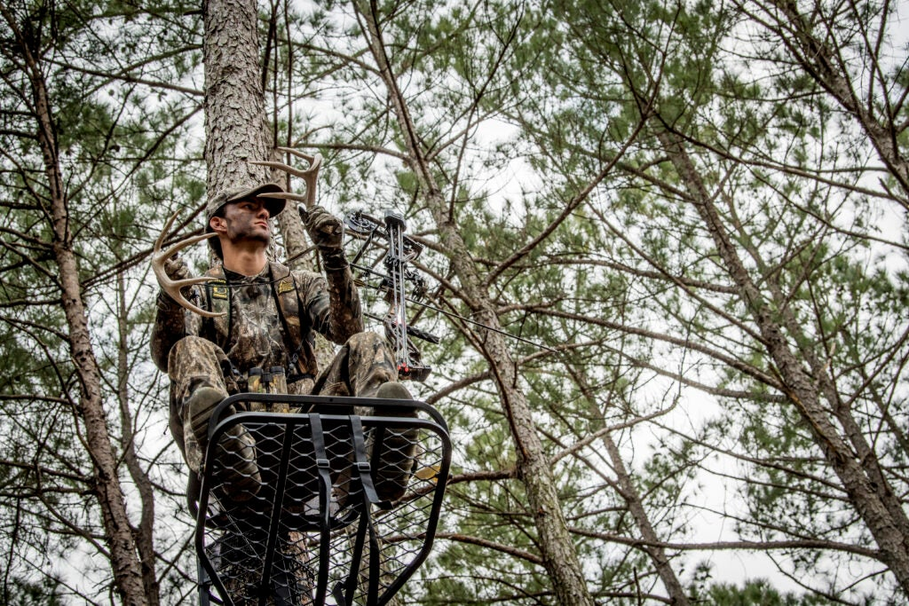 Man hunting deer sitting in a treestand rattling two antlers.