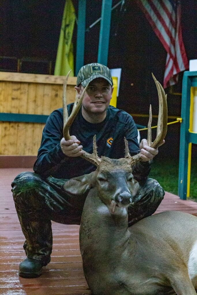 in deck man poses for picture with deer with big rack