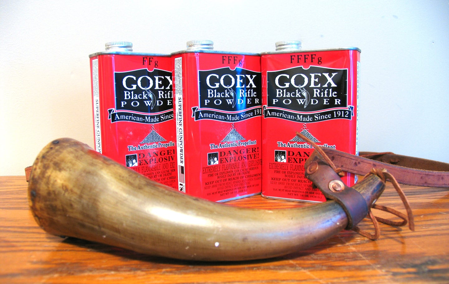 Three cans of GOEX Black powder on a table with a powder horn.