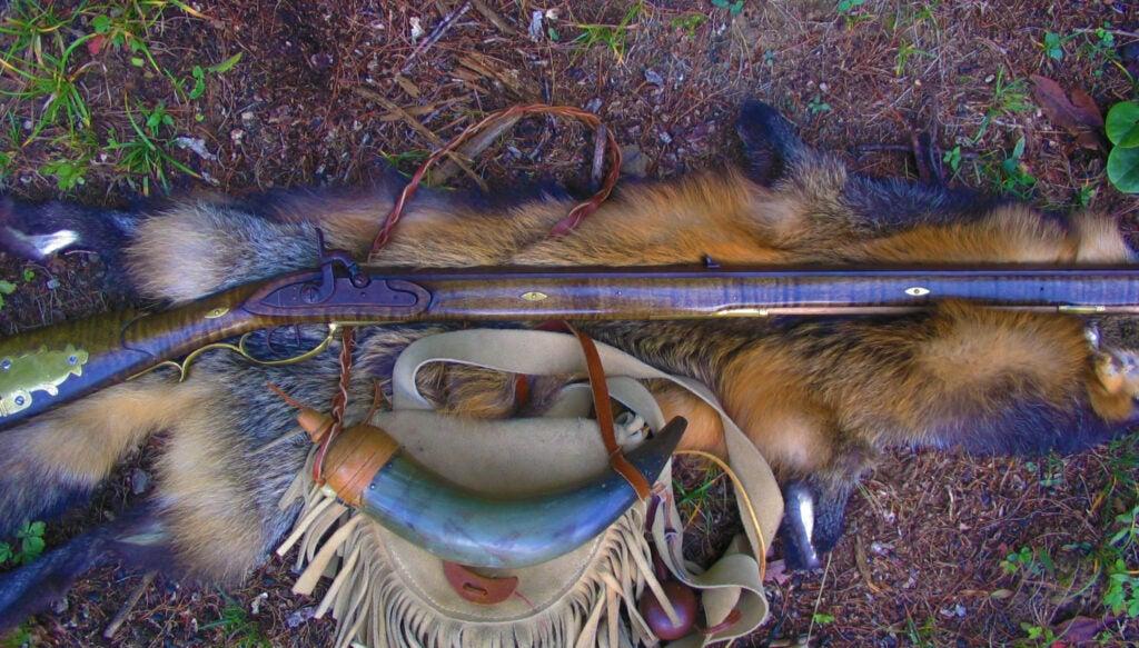 Traditional black powder rifle on a pelt with a powder horn.