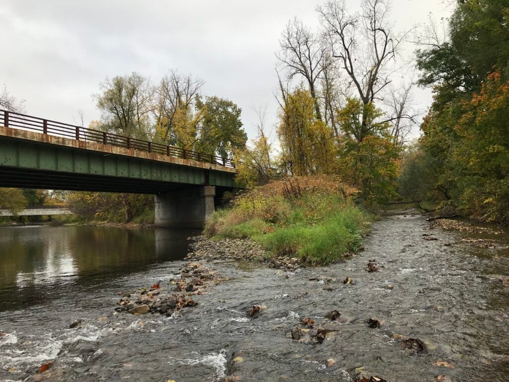 stream running next to a bridge.
