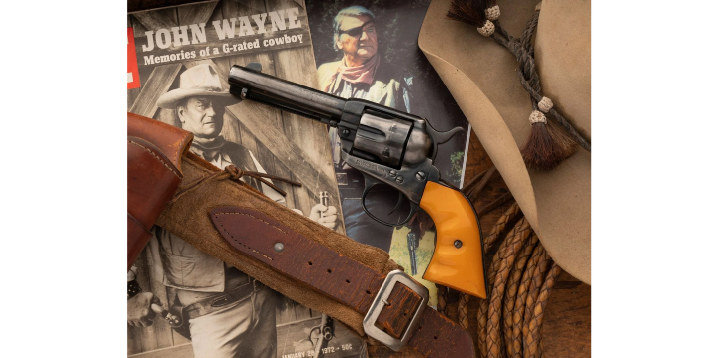 John Wayne Revolver and holster on a table with memorabilia.