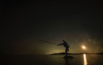 A surf fisherman casts into the night.