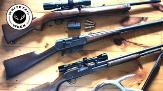 Three classic deer rifles on a table with ammo and an antler.